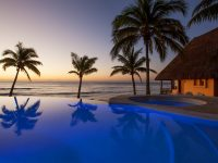 Sunset overlooking resort-style infinity pool and the Caribbean at Mahekal Beach Resort